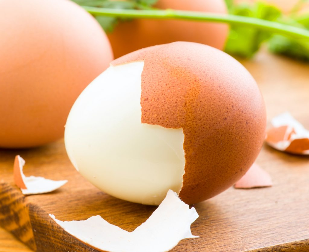 Boiled eggs with one half peeled