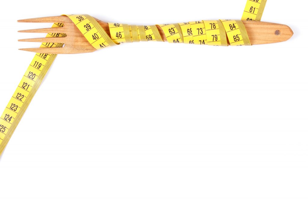 Tape measure around a fork, indicating lose weight