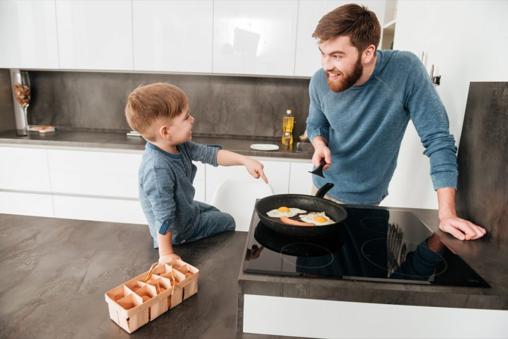 Handsome bearded father cooking at kitchen with his cute son