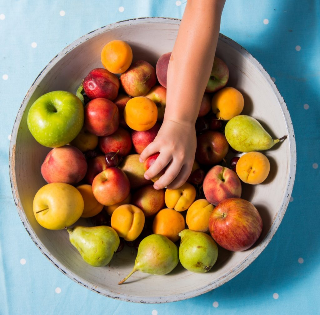 taking a fruit from a bowl, on a blue table runner