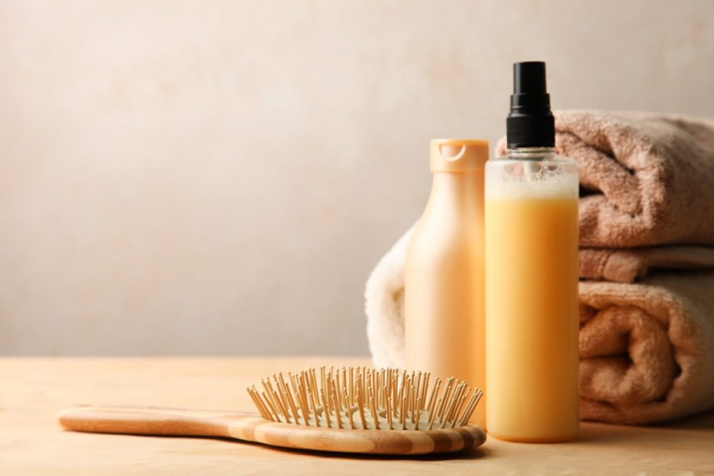 Hair care products on wooden table on neutral background.