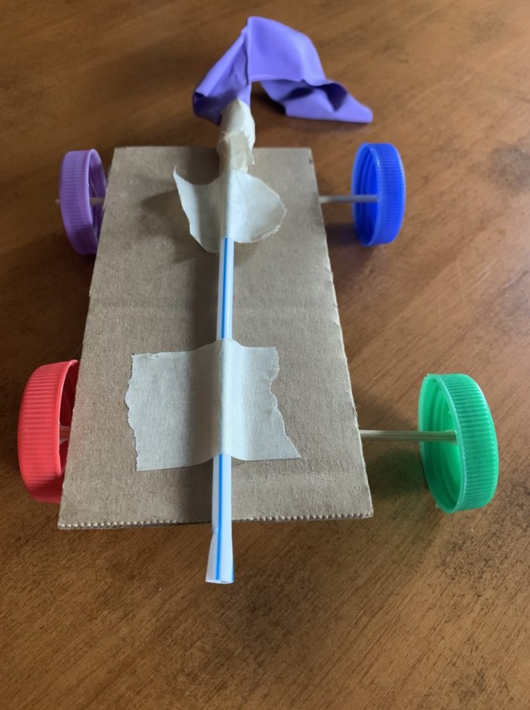 homemade toy car made with cardboard, straws and bottle caps