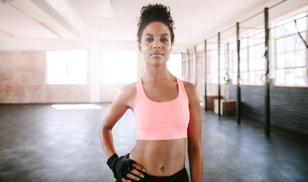 Confident young woman standing in gym